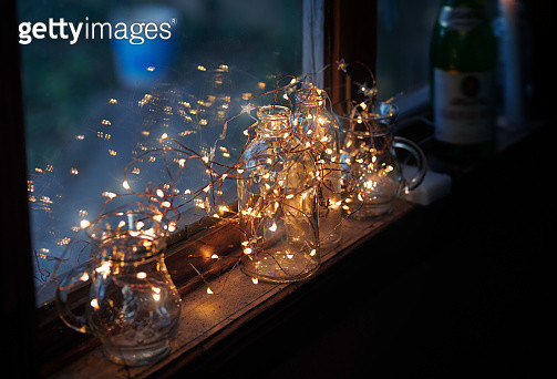 Window sill decorated with glassware and Christmas string light - gettyimageskorea