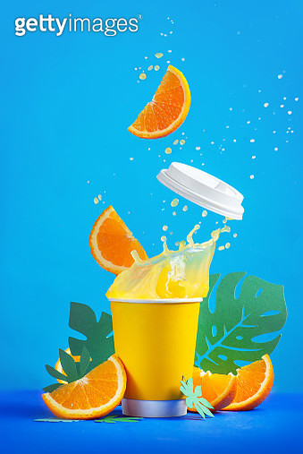 Orange juice dynamic splash in a paper cup with flying orange slices and tropical leaves, Action food photography on a bright blue background with copy space. Summer refreshing drink. - gettyimageskorea