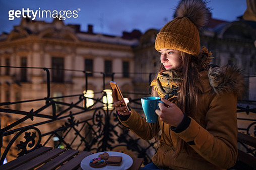 Teenage girl enjoying city view at night. The girl is sitting on balcony, drinking tea and posting photos on social media.Nikon D850 - gettyimageskorea