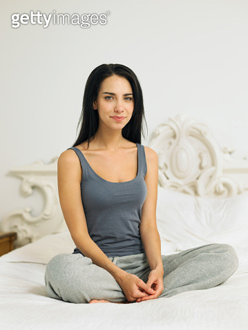Young woman sitting cross legged on bed, portrait - gettyimageskorea