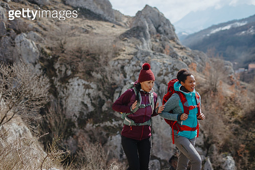 Female hikers with backpacks enjoying the view in the mountains - gettyimageskorea