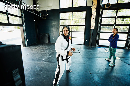 Female Muslim self defense instructor preparing to demonstrate kick during class in gym - gettyimageskorea