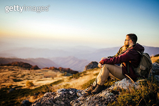 Romantic couple in love sitting on rock in nature and talking during hiking, taking a rest together - gettyimageskorea