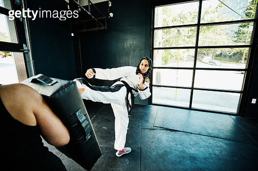 Female Muslim self defense instructor demonstrating kick during class in gym - gettyimageskorea