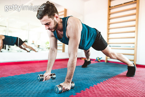 fitness man doing pushups with the dumbell - gettyimageskorea