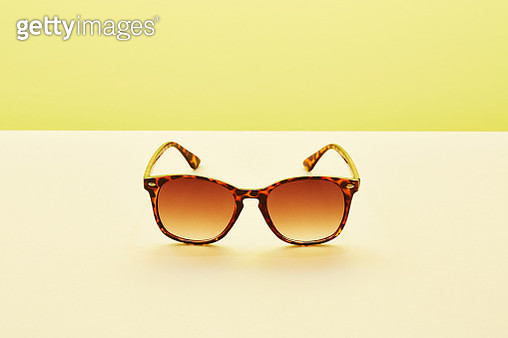 A pair of sunglasses against a yellow background - gettyimageskorea