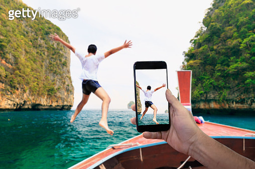 Smartphone photographing Asian young man jumping from boat into the Andaman Sea, Thailand - gettyimageskorea