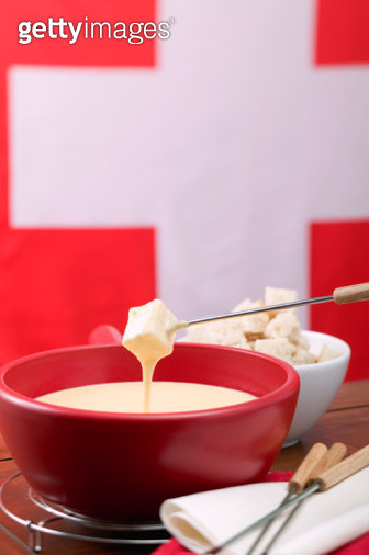 Cheese fondue in front of Swiss flag, close up - gettyimageskorea