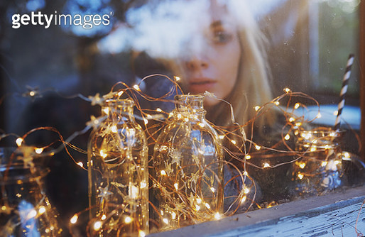 Woman at home looking through the window decorated for Christmas - gettyimageskorea