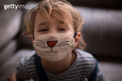 Boy wearing a surgical mask painted as a cat - gettyimageskorea