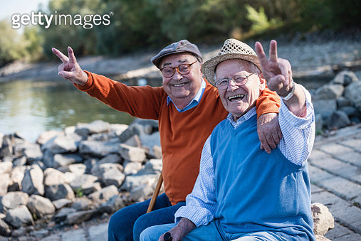Two old friends sitting by the riverside, having fun - gettyimageskorea