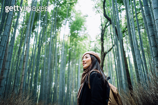 Beautiful young Asian female backpacker enjoying in nature. She is walking along the pathway in the bamboo grove of Arashiyama, Kyoto, exploring and enjoying the spectacular nature scenics - gettyimageskorea