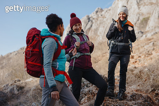 Female hikers enjoying the view in the mountains while having a chat - gettyimageskorea