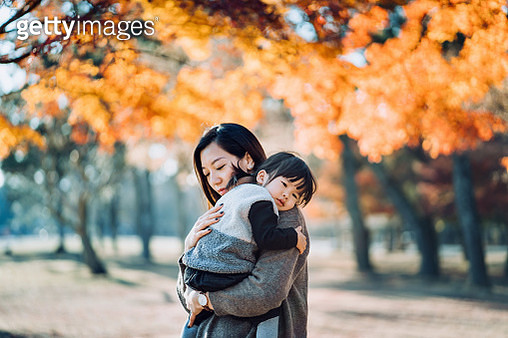 A loving young Asian mother embracing adorable little daughter in arms, spending time together and enjoying the beautiful Autumn scenics in nature park on a beautiful sunny day - gettyimageskorea