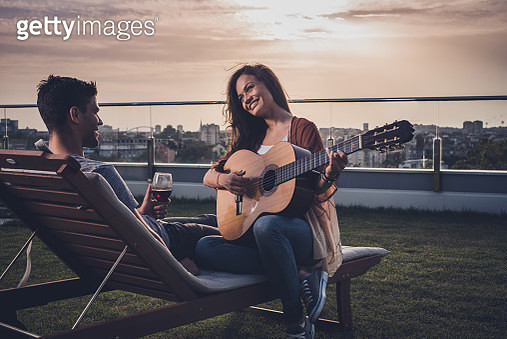 Happy couple in love spending romantic moments with guitar and wine on a penthouse balcony. - gettyimageskorea