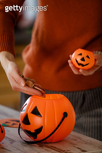 Woman putting candy in a plastic pumpkin, preparing for traditional Halloween festival, close up. - gettyimageskorea