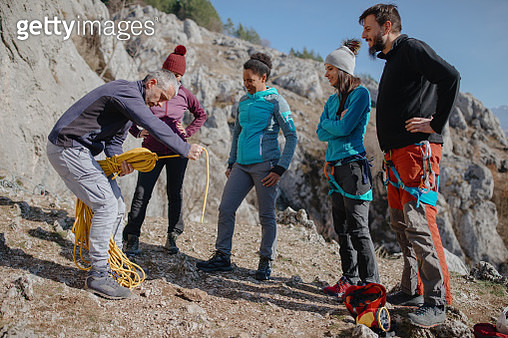 Climb instructor packs a rope in front of the climbing group - gettyimageskorea