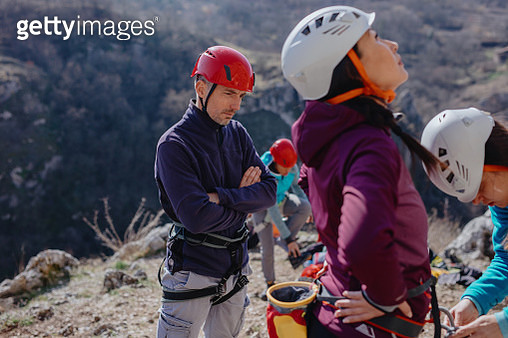 Instructor checking climbing harness before letting her climb group goes sport climbing - gettyimageskorea