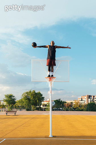 Black player standing on basketball hoop and stretching arms - gettyimageskorea