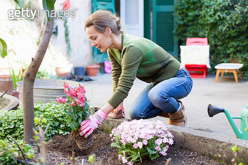 Woman planting flowers in her backyard, Rome, Italy - gettyimageskorea