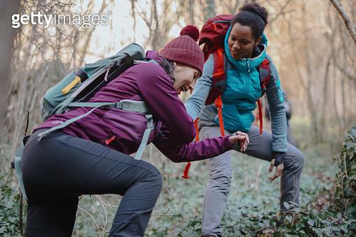 Hiker giving her hand helping partner climb up - gettyimageskorea