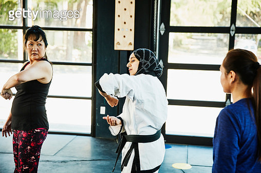 Female Muslim self defense instructor showing students technique during class in gym - gettyimageskorea