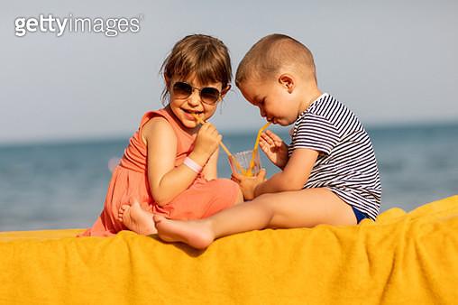 Cute little baby boy and a girl drinking orange juice using drinking straws. Children enjoying beach life on a sunny summer day - gettyimageskorea