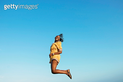 Low Angle Portrait Of Cheerful Woman Jumping Against Clear Blue Sky - gettyimageskorea