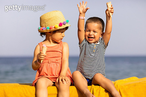 Beautiful children holding and eating ice cream on a sunny summer day. brother and sister enjoying beach life - gettyimageskorea
