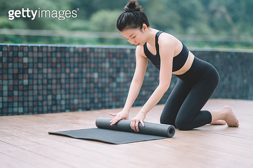 an yoga instructor rolling up the yoga mat at front yard of her house - gettyimageskorea