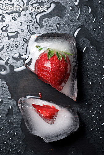 Overhead view of chopped frozen strawberry on wet table - gettyimageskorea