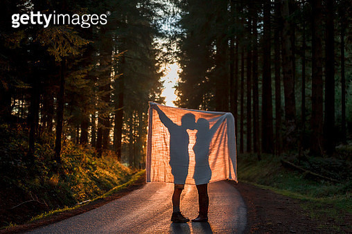 Silhouette of couple holding blanket kissing on country road in forest - gettyimageskorea