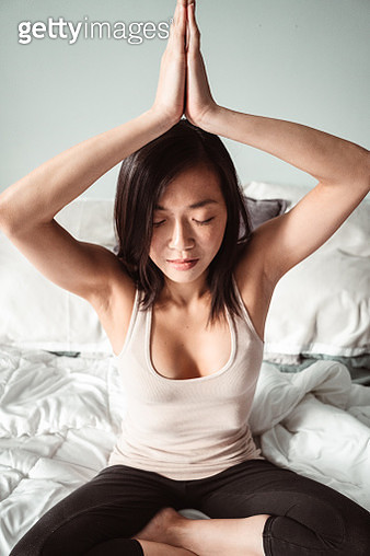 chinese woman doing yoga in the bed - gettyimageskorea