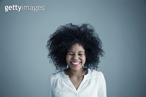 Portrait enthusiastic mixed race young woman with curly black afro hair laughing with eyes closed - gettyimageskorea