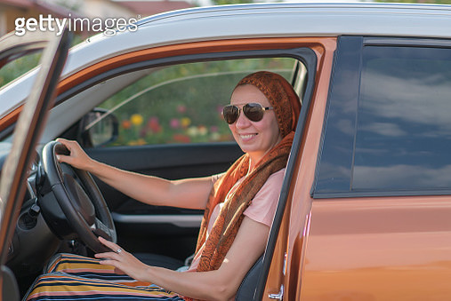 Modern muslim woman driving a car - gettyimageskorea