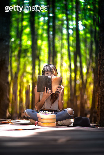 young student woman atend reading a book in the rain forest at light of the sunshade - gettyimageskorea