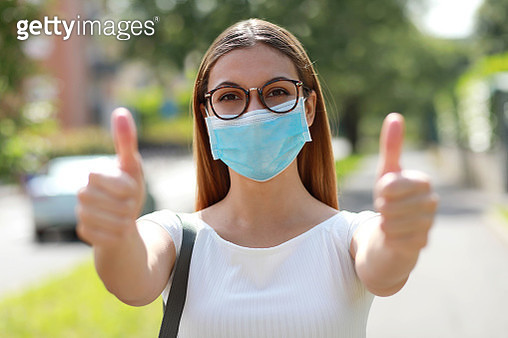 Portrait Of Woman Wearing Mask Showing Thumbs Up - gettyimageskorea