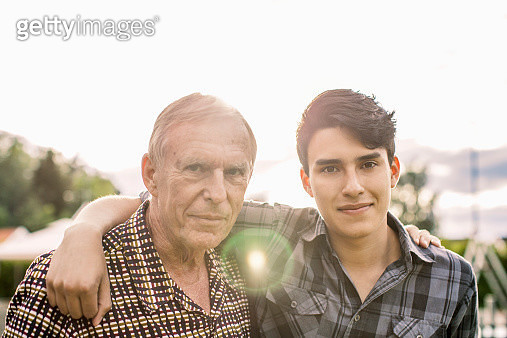 Portrait of confident grandfather and grandson with arms around against sky - gettyimageskorea