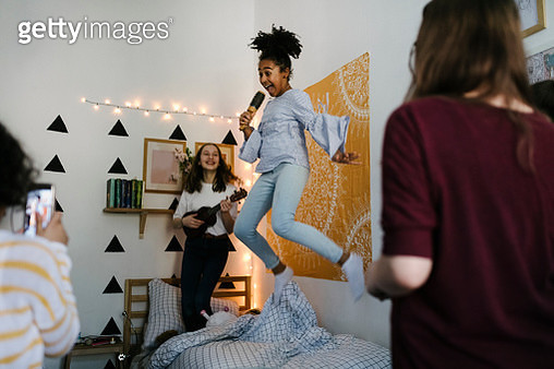Black tween jumping in the air while singing into hairbrushes at slumber party. - gettyimageskorea