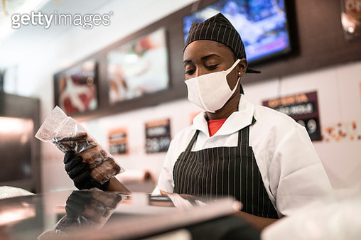 Female butcher talking to customer at butcher's shop - gettyimageskorea