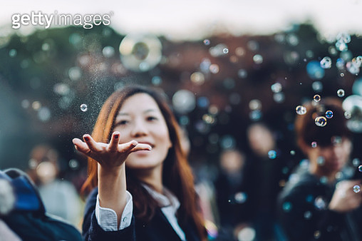 Young woman catching bubbles joyfully in park - gettyimageskorea
