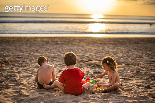Group of small kids relaxing in sand on the beach. It's beautiful sunset. - gettyimageskorea