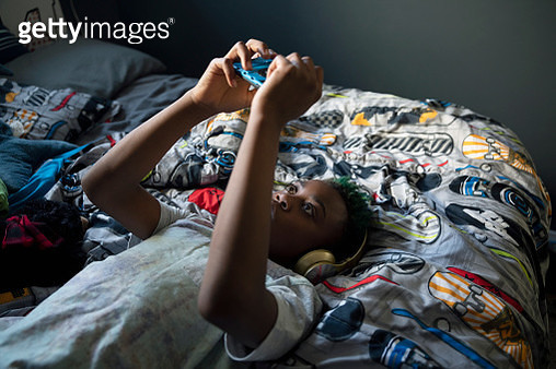 Boy with headphones and mp3 player listening to music, laying on bed - gettyimageskorea