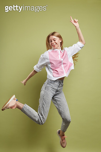 Young beautiful woman with long blond hair wearing white blouse and blue jeans jumping for joy. Shot in studio on green background - gettyimageskorea