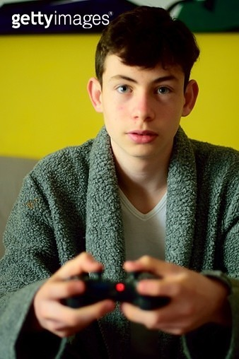 Teen boy playing video games on the sofa at home - gettyimageskorea