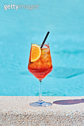 Wine Glass Of Cold Cocktail Spritz Against Turquoise Water Of Poolside - gettyimageskorea