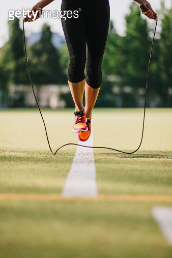 Woman doing jump roping on a sports field. - gettyimageskorea