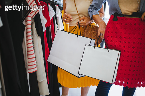 Mature women holding shopping bags and shopping in clothes store - gettyimageskorea