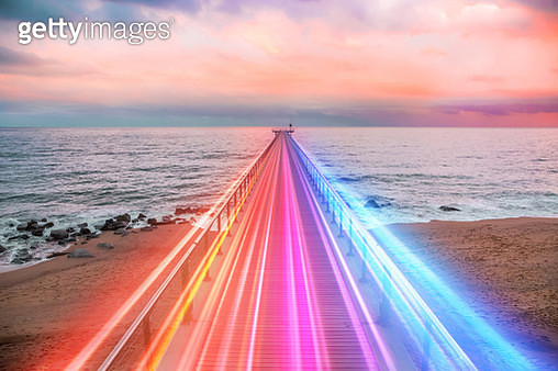 Creative composition of colorful lights trails in motion over the sea. - gettyimageskorea