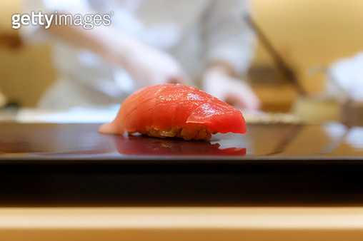Closeup fatty blue fin or red tuna sushi serving on a black plate, in a Japanese comaker or traditional way of sushi-serving style. There is chef wearing white costumes cutting raw fishes at the background. Omakase style of sushi serving represents luxury - gettyimageskorea
